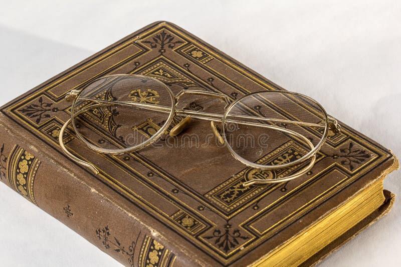 Occhiali antichi che si siedono su un innario d'annata su un fondo bianco fotografia stock libera da diritti