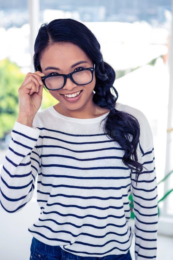 Occhiali asiatici sorridenti della tenuta della donna fotografia stock libera da diritti