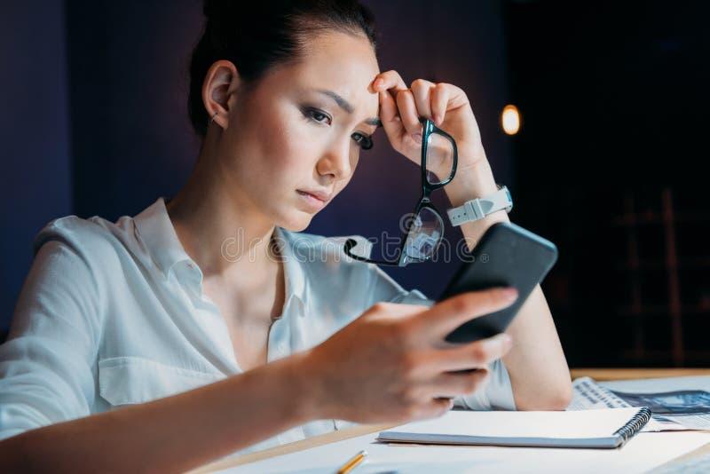Occhiali asiatici stanchi pensierosi della tenuta della donna di affari e smartphone usando fotografia stock libera da diritti