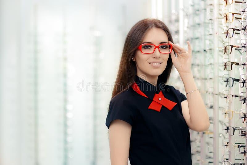 Occhiali d'uso della donna di modo in negozio ottico medico fotografia stock