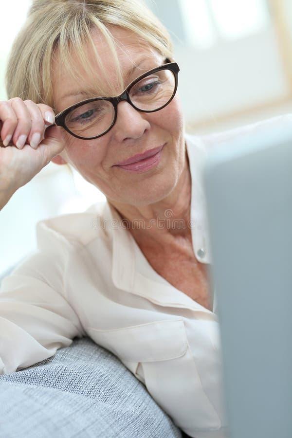 Occhiali d'uso della donna senior e websurfing fotografia stock libera da diritti
