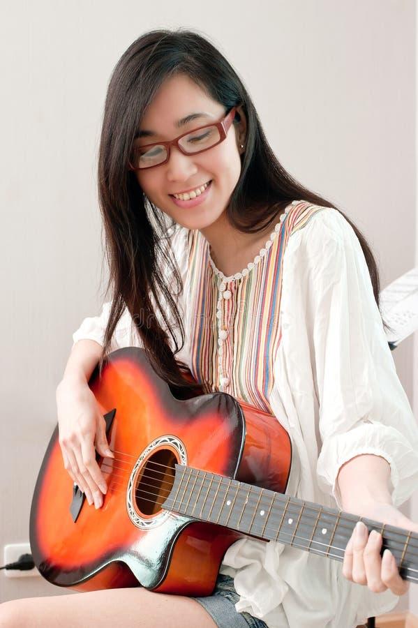 Occhiali d'uso sorridenti e gioco della bella ragazza asiatica della chitarra nella stanza di musica immagini stock libere da diritti