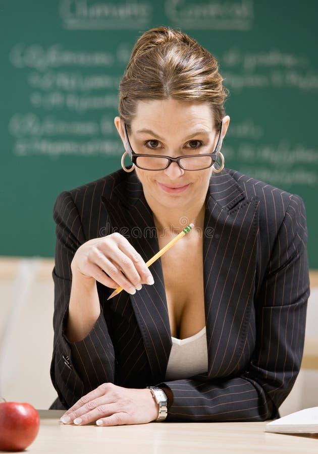 Occhiali da portare dell'insegnante che tengono matita immagini stock