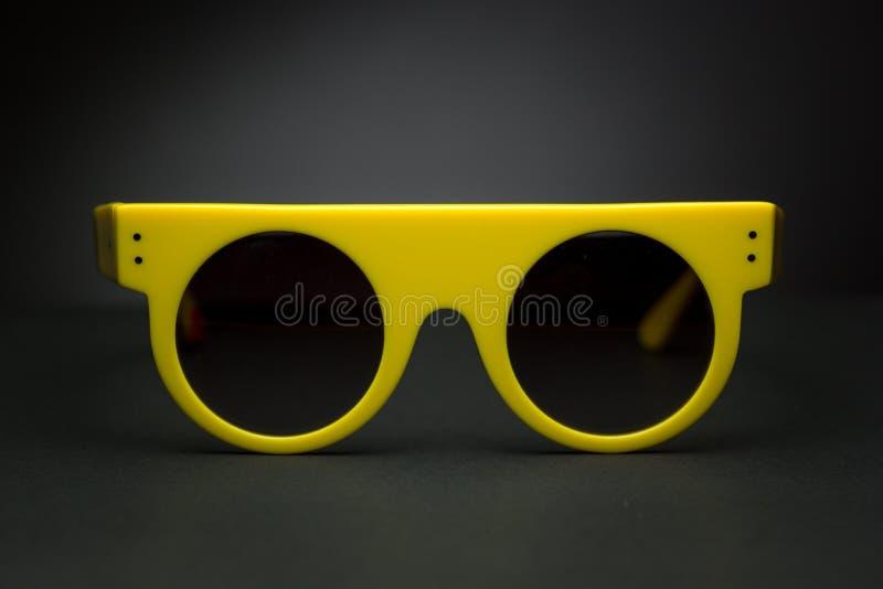 Occhiali da sole alla moda per estate su fondo nero immagine stock