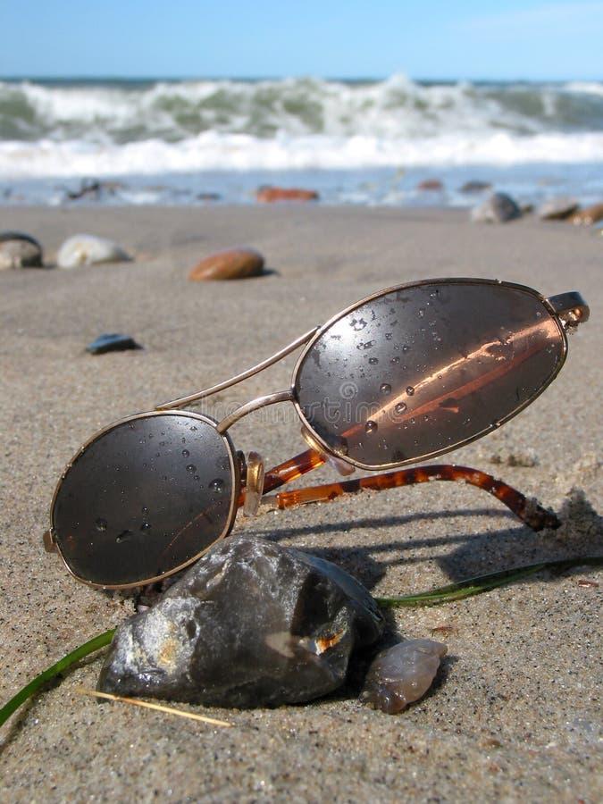 Occhiali da sole bagnati sulla spiaggia fotografia stock