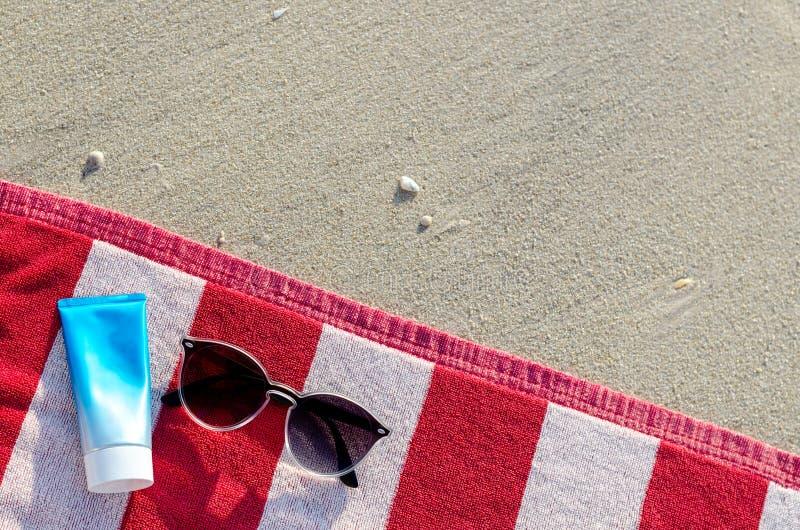 Occhiali da sole con la lozione e la borsa della protezione solare sull'asciugamano rosso immagine stock libera da diritti