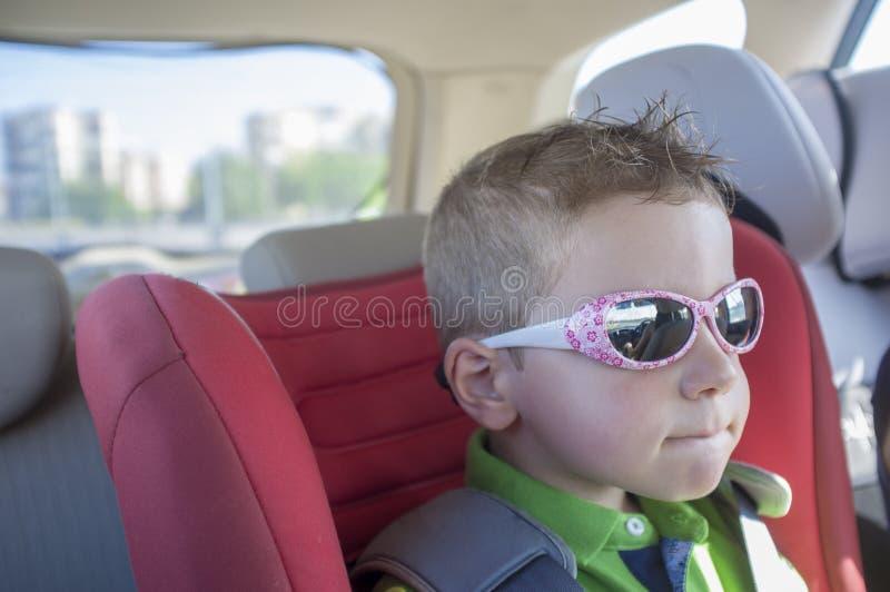 Occhiali da sole d'uso del ragazzo bello del bambino dentro l'automobile immagini stock