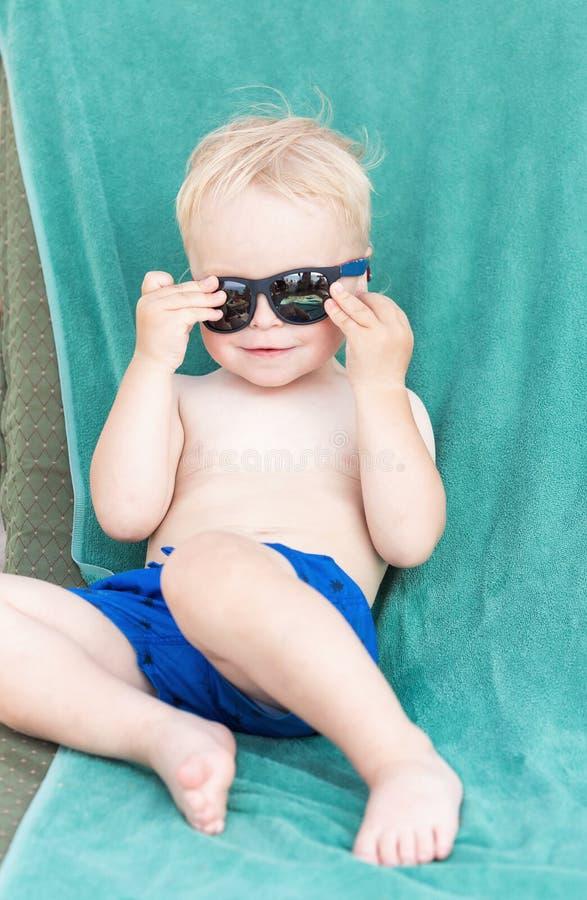 Occhiali da sole d'uso del ragazzo biondo del bambino fotografia stock