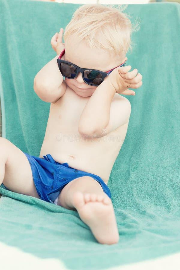Occhiali da sole d'uso del ragazzo biondo del bambino fotografie stock libere da diritti