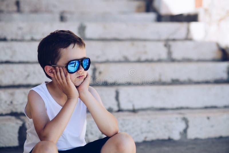Occhiali da sole d'uso del ragazzo del piccolo bambino e sedersi sulle vecchie scale immagine stock