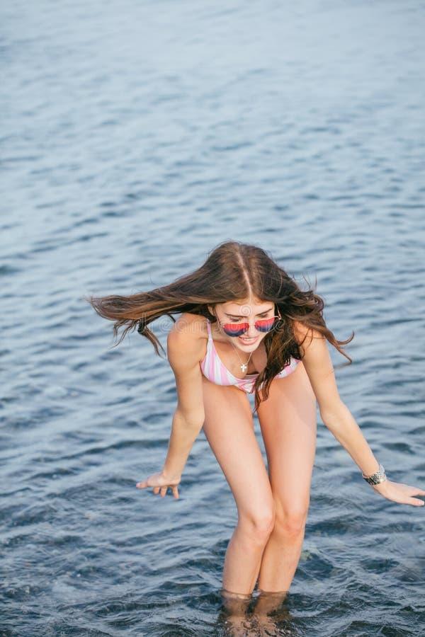 Occhiali da sole d'uso della bella donna in mare che spruzza acqua fotografia stock libera da diritti