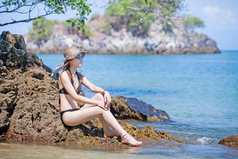 Occhiali da sole d'uso della donna asiatica in bikini che si rilassa sulla spiaggia immagini stock