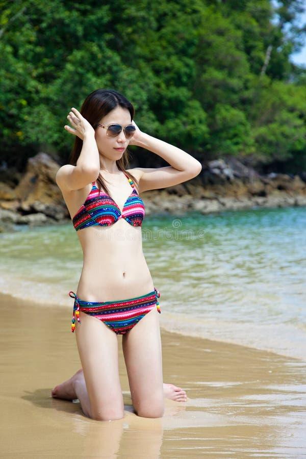 Occhiali da sole d'uso della donna asiatica in bikini che si rilassa sulla spiaggia di sabbia fotografie stock