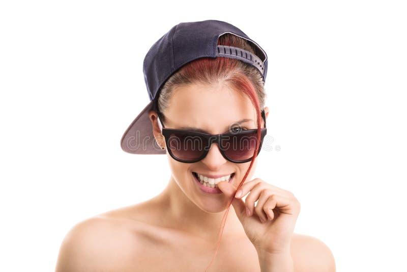 Occhiali da sole d'uso della ragazza e un cappello di sport fotografia stock
