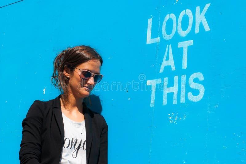 Occhiali da sole d'uso di modello dei pantaloni a vita bassa che posano accanto a Lo immagine stock