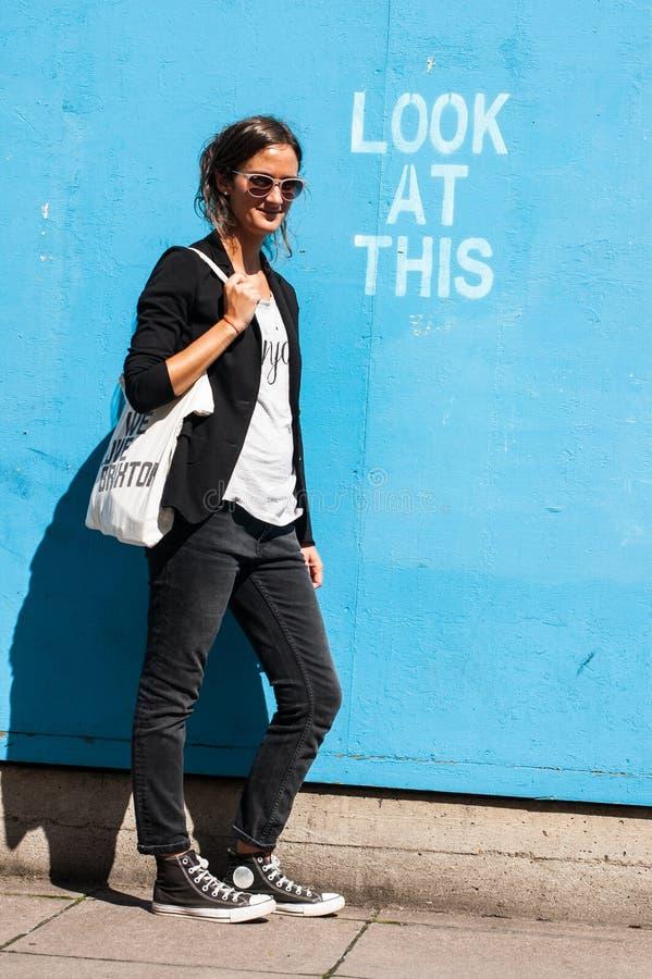 Occhiali da sole d'uso di modello dei pantaloni a vita bassa che posano accanto a Lo fotografie stock