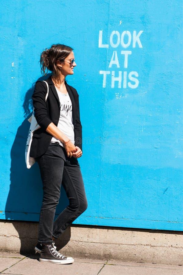 Occhiali da sole d'uso di modello dei pantaloni a vita bassa che posano accanto a Lo fotografia stock libera da diritti