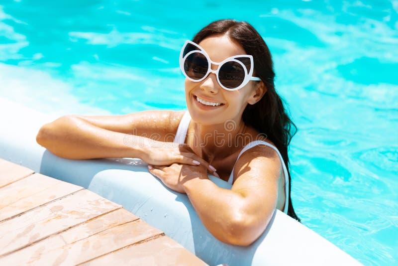 Occhiali da sole d'uso d'orientamento della donna che raffreddano nello stagno fotografia stock