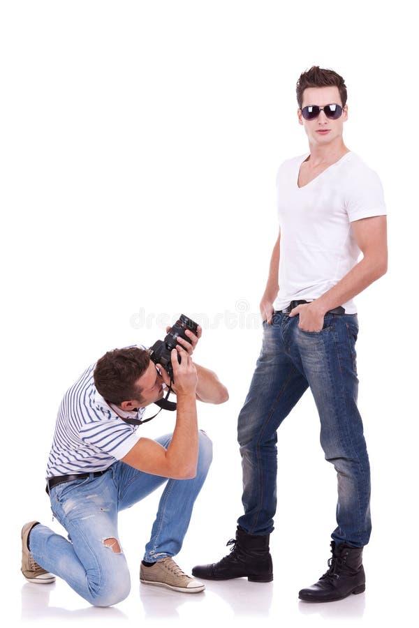 Occhiali da sole da portare del giovane che sono fotografati fotografia stock