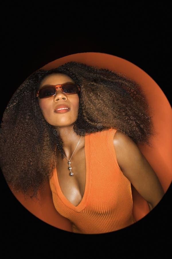 Occhiali da sole da portare della giovane donna del African-American. fotografia stock libera da diritti