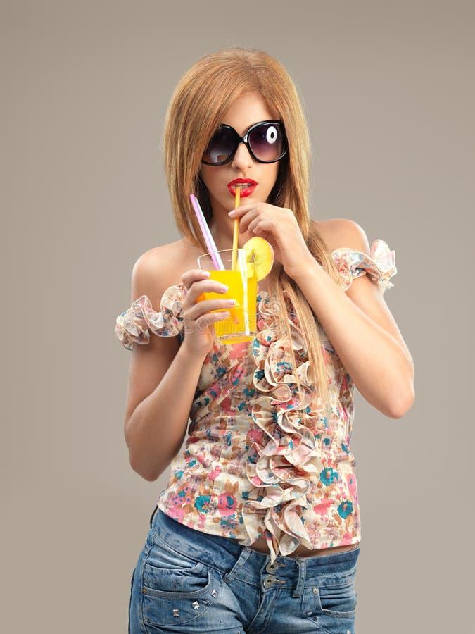 Occhiali da sole della donna del ritratto che bevono cocktail immagine stock