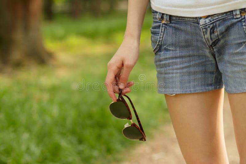 Occhiali da sole della tenuta della mano della donna fotografia stock