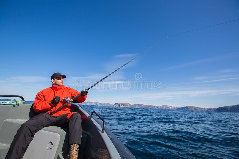 Occhiali da sole dello sportivo del pescatore che pescano nel mare immagini stock