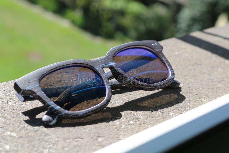Occhiali da sole di legno di modo su una superficie della roccia immagine stock