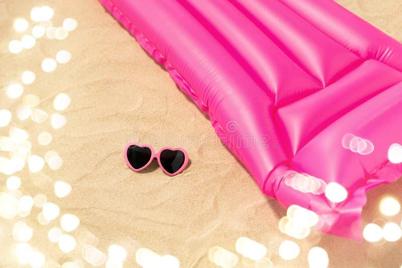 Occhiali da sole e materasso di nuoto rosa sulla spiaggia fotografie stock