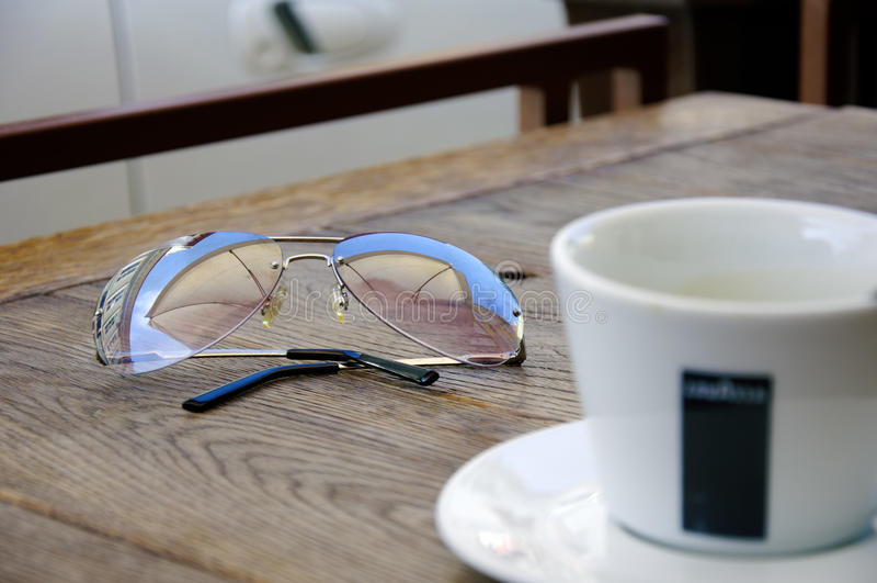 Occhiali da sole e una tazza di caffè fotografie stock libere da diritti