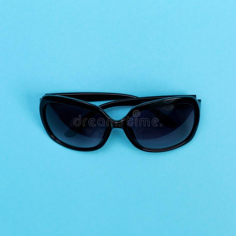 Occhiali da sole freschi su un fondo del blu di bambino immagini stock
