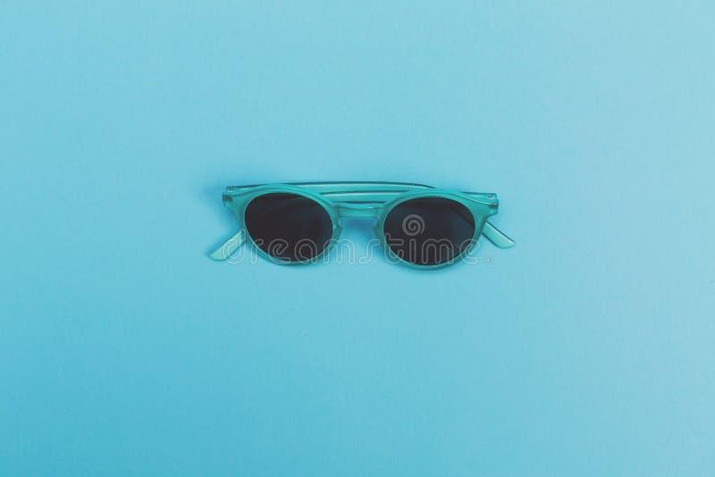 Occhiali da sole freschi su un fondo del blu di bambino fotografia stock