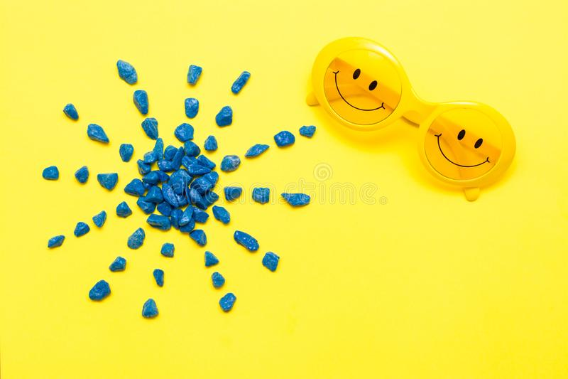 Occhiali da sole gialli di plastica con gli occhi dipinti e un sorriso sui vetri e pietre blu decorative sotto forma del sole fotografia stock libera da diritti
