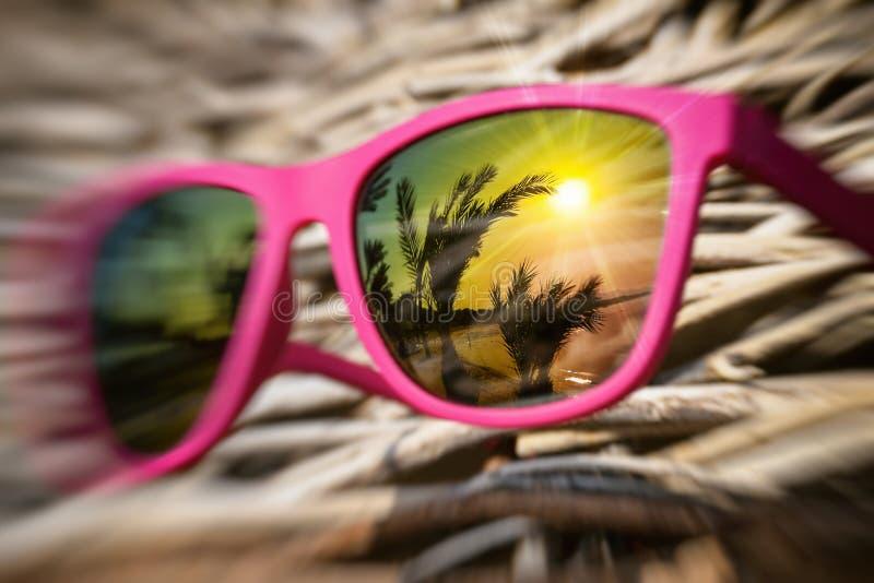 Occhiali da sole rosa alla moda su un ombrello di legno con la bella riflessione nel vetro variopinto immagini stock