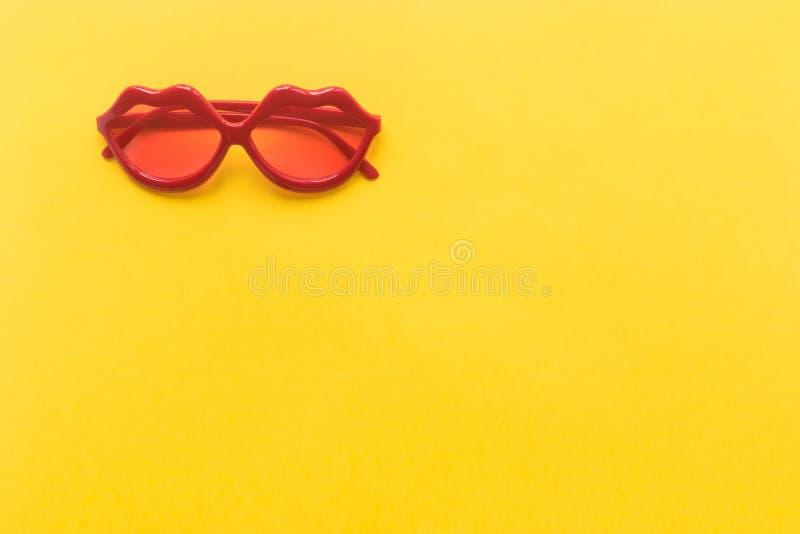 Occhiali da sole rossi di modo su fondo giallo Orli fotografie stock