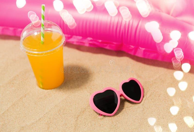 Occhiali da sole, succo e materasso dello stagno sulla sabbia della spiaggia fotografie stock
