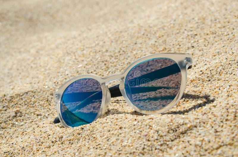 Occhiali da sole sulla spiaggia Multi modello alla moda colorato con la struttura trasparente e le lenti blu Concetto di vacanza fotografia stock libera da diritti