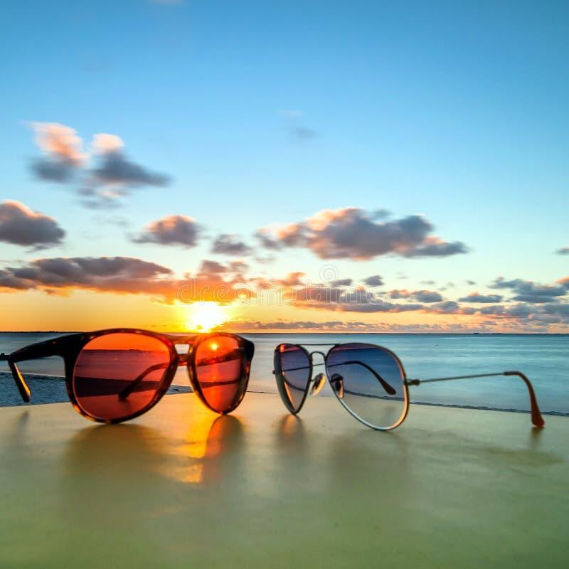 Occhiali da sole sulla tavola tropicale della spiaggia al tramonto fotografie stock