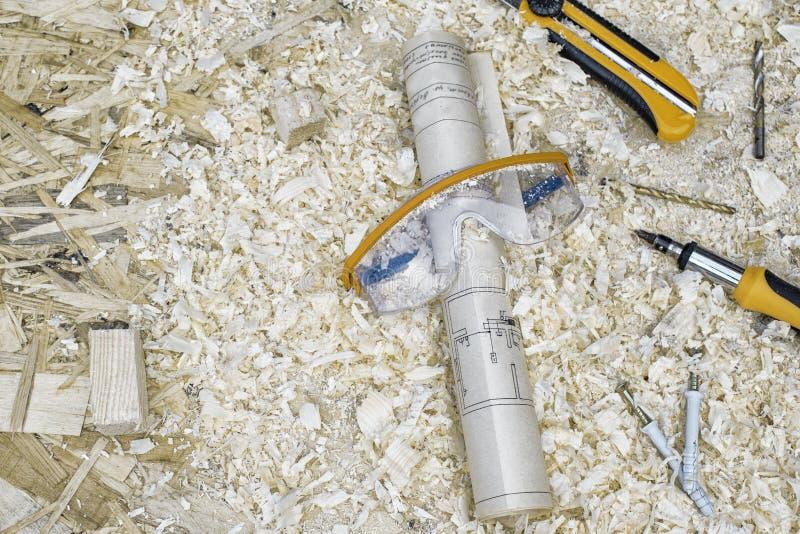 Occhiali di protezione con il piano, il cacciavite ed il coltello della costruzione sui precedenti del concetto della segatura su fotografia stock