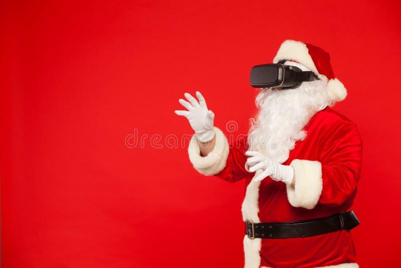 Occhiali di protezione d'uso di realtà virtuale di Santa Claus, su un fondo rosso Natale immagini stock libere da diritti
