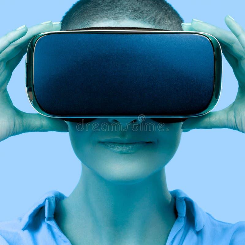 Occhiali di protezione d'uso di realtà virtuale della giovane donna Donna che indossa i vetri di VR sopra fondo blu Concetto di e immagini stock
