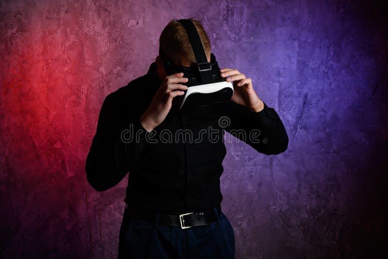 Occhiali di protezione d'uso di realt? virtuale dell'uomo brutale in studio Usando con la cuffia avricolare di VR fotografia stock libera da diritti