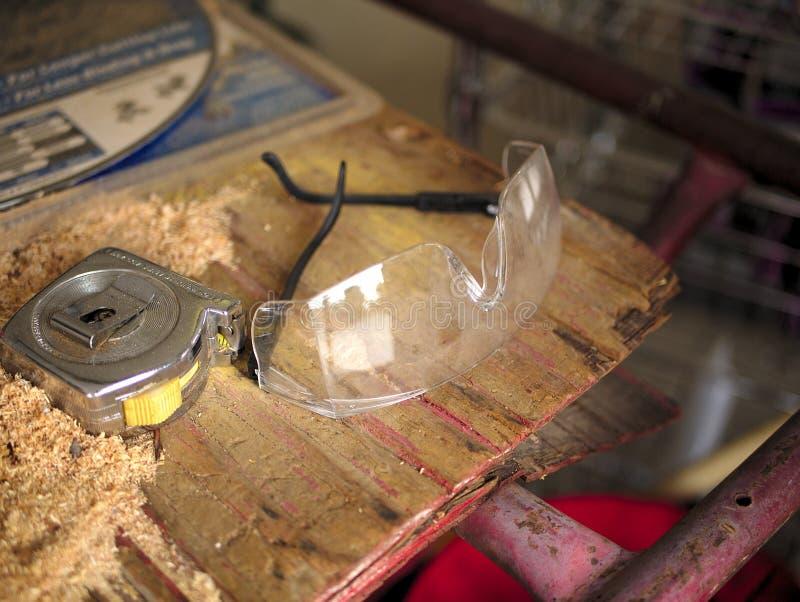 Occhiali di protezione della costruzione e nastro di misurazione fotografia stock libera da diritti