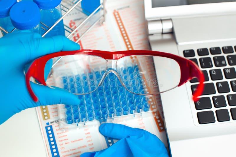Occhiali di protezione della tenuta dello scienziato nella tavola di lavoro del labora fotografia stock