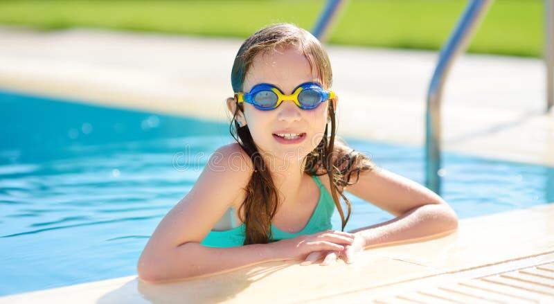 Occhiali di protezione di nuoto d'uso della ragazza sveglia divertendosi nello stagno all'aperto Apprendimento nuotare Bambino di immagine stock libera da diritti
