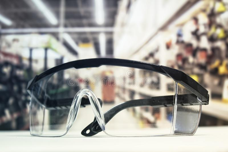 Occhiali di protezione di plastica, sulla tavola e sui precedenti della ferramenta con gli strumenti immagini stock