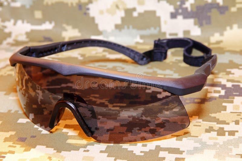 Occhiali di protezione tattici militari sul primo piano preso fondo del cammuffamento immagine stock