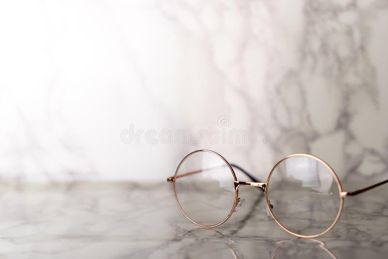 Occhiali dorati d'annata sulla pietra di marmo di lusso fotografie stock libere da diritti