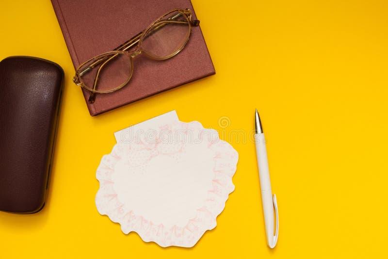 Occhiali, il libro, una nota su un fondo giallo fotografia stock libera da diritti