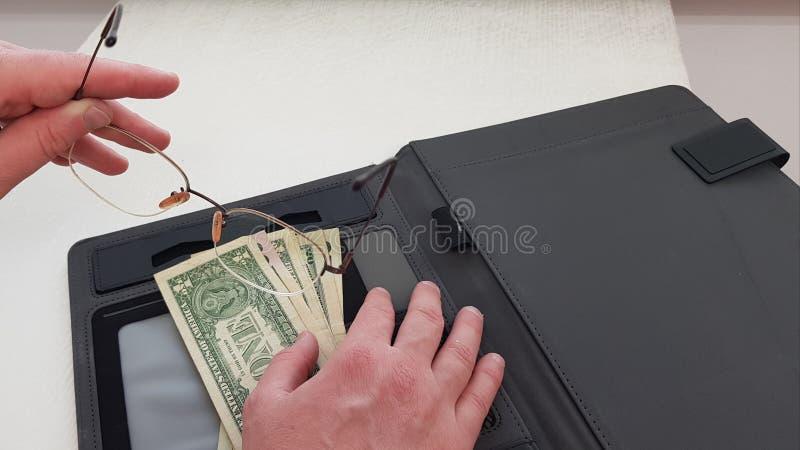 Occhiali in mano sinistra maschio mentre la sua mano destra mette sui dollari americani fotografie stock libere da diritti
